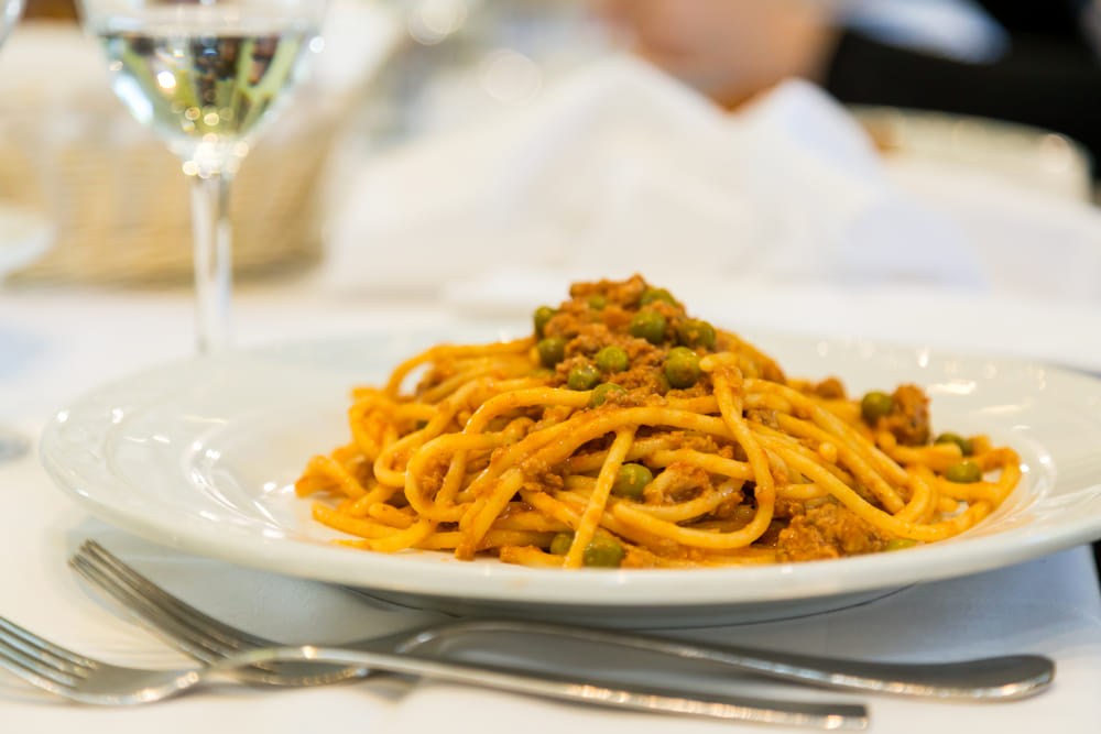 Spaghetti bolognesi with ragù and peas
